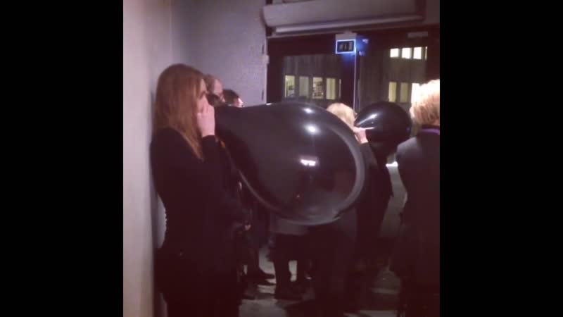 Girl blowing to pop large black balloon in a crowded confined space for the sake of art